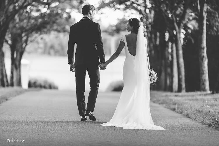 Married Couple On Wedding Day Walking Down Path
